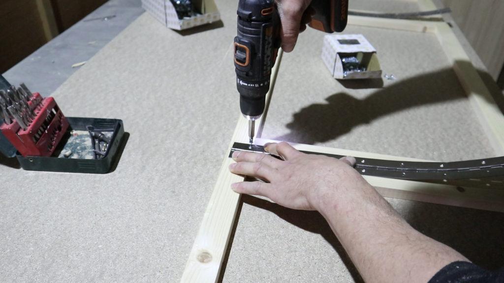 atornillando las bisagras en la estructura de madera