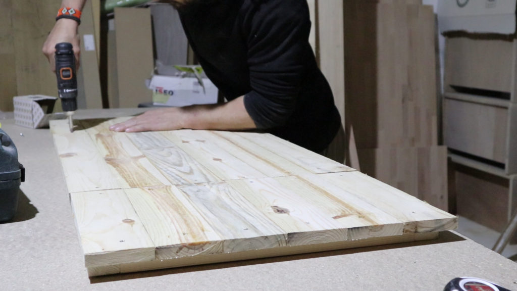 atornillando las tablas de los palets en la estructura de nuestra mesa con un destornillador eléctrico
